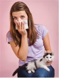 Young woman holding a kitten and sneezing into a tissue.